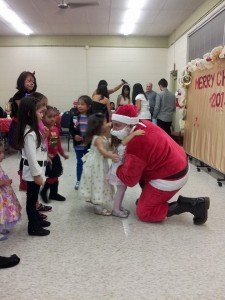 As soon as Santa appears, the kids rushed to the front and these two little girls gave him hugs first. :)