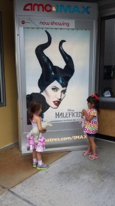 These two little girls are excited to watch a movie in the big screen.
