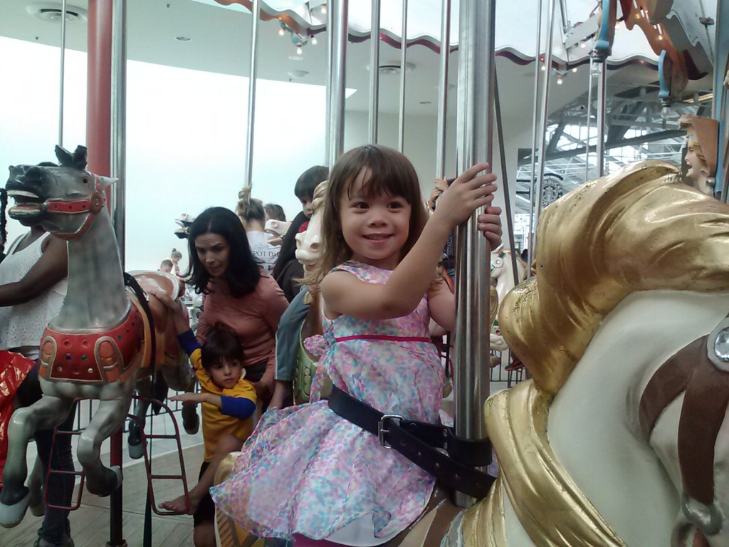K was very happy riding the carousel.