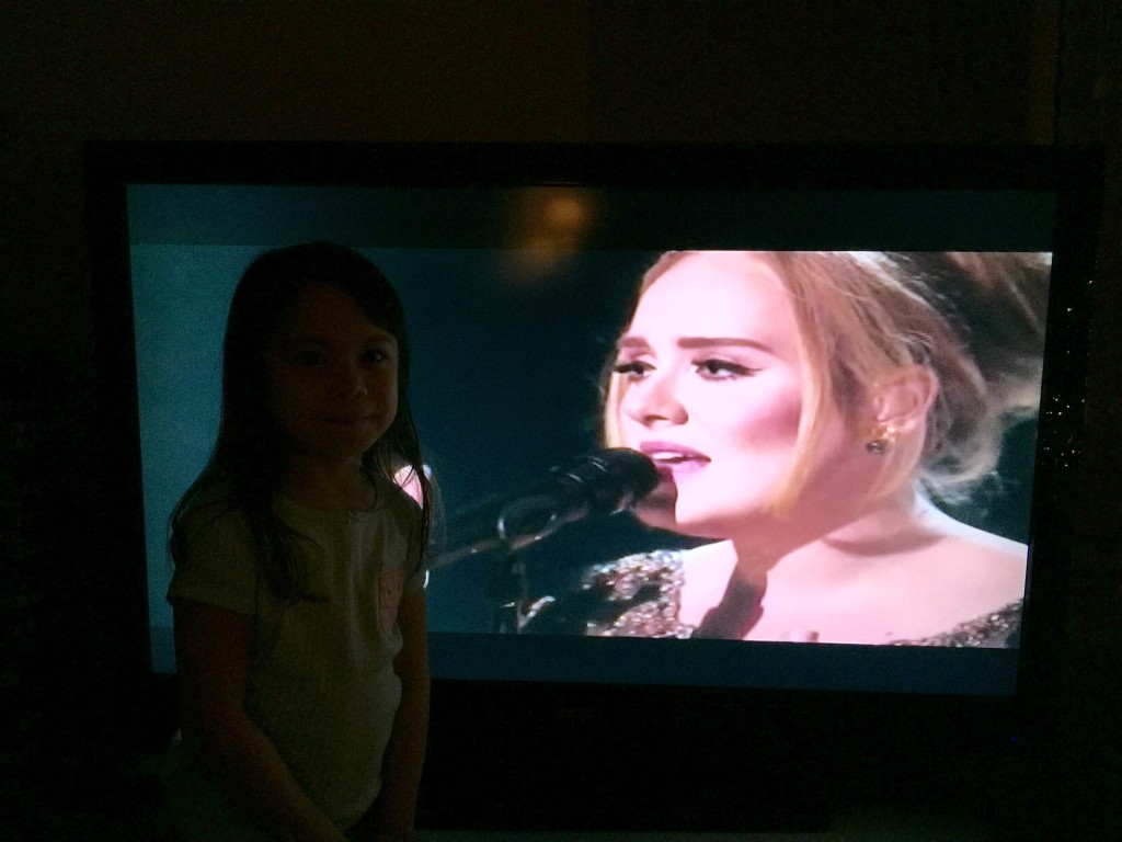 Adele on the screen and my darling K next to her image. K wanted to take her photo with #Adele. :)